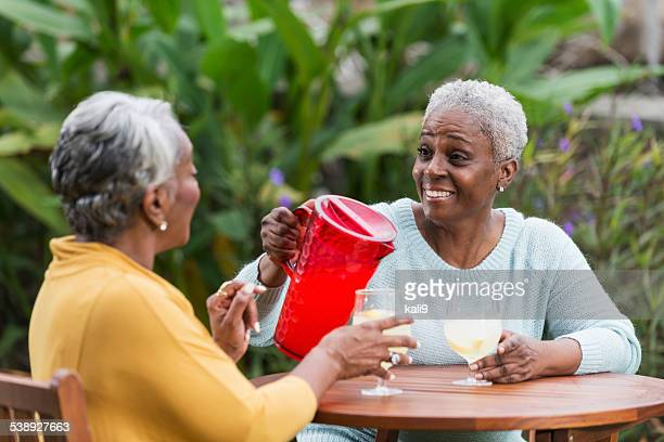 Senior woman pouring drink for a friend