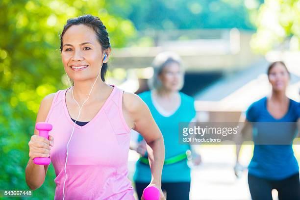 Senior woman power walks in park
