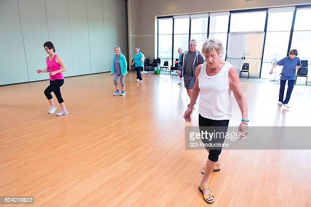 Senior woman practices dance in studio of senior center