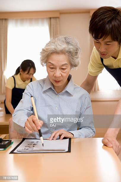 Senior woman practicing calligraphy, male nurse looking on the side