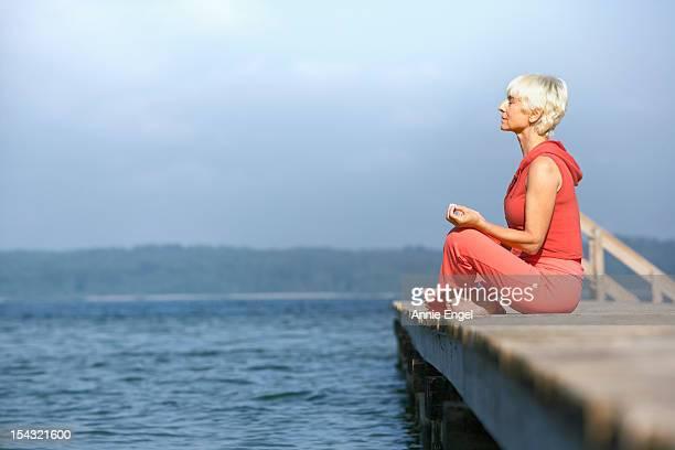 Senior woman practicing yoga on jetty