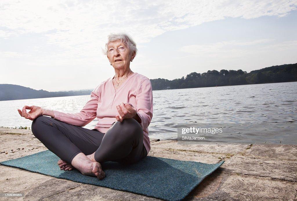 senior woman practising yoga at lake