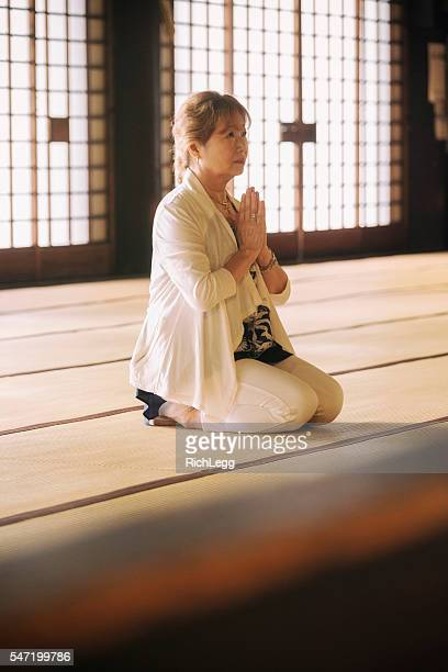 Senior Woman Praying in Buddhist Temple