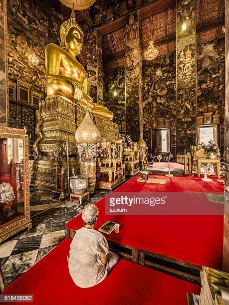Senior woman praying in Wat Suthat Bangkok