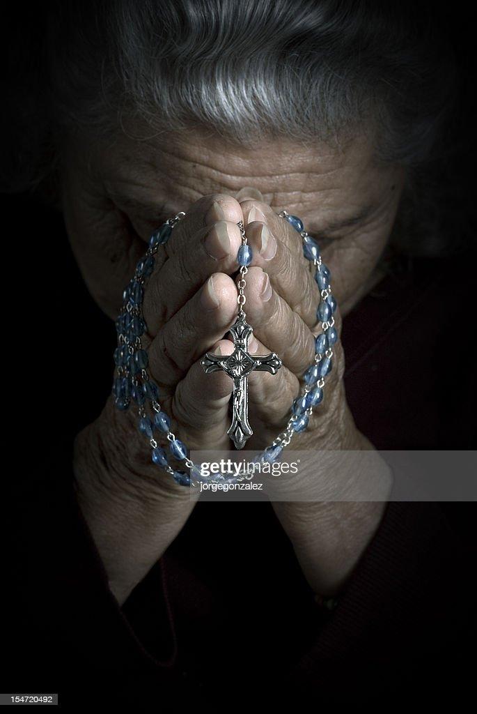 Senior Woman Praying with Rosary : Stock Photo