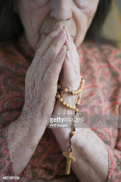 Senior woman praying with rosary