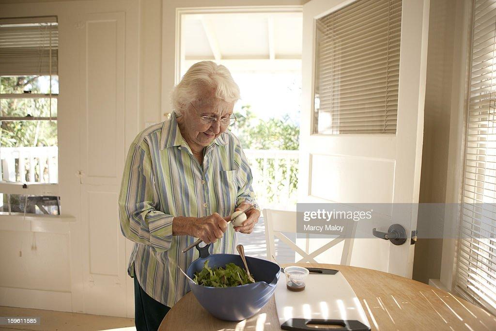 Senior woman preparing a salad.