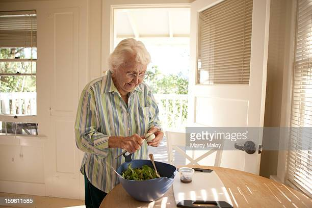 Senior woman preparing a salad.