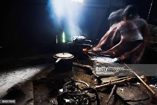 Senior woman preparing food in a kitchen, Jinkeng Terraced Field, Guangxi Province, China