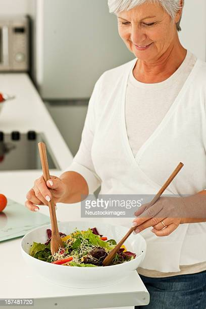 Senior woman preparing salad in kitchen