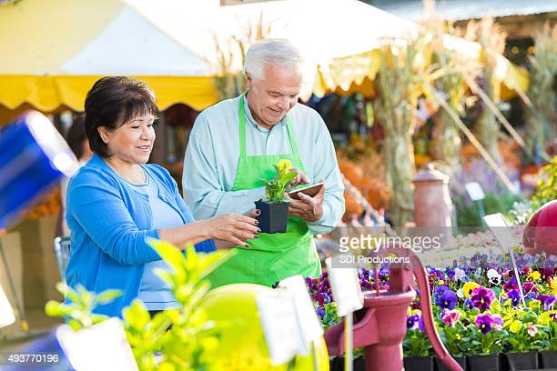Senior woman purchasing plants with assistance of gardening store owner