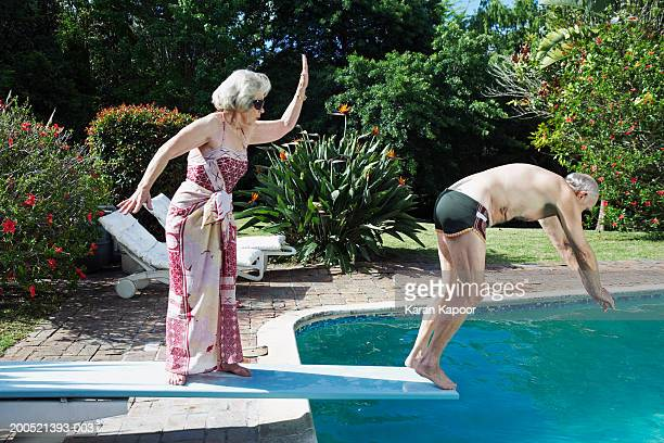 Senior woman pushing senior man off diving board, side view