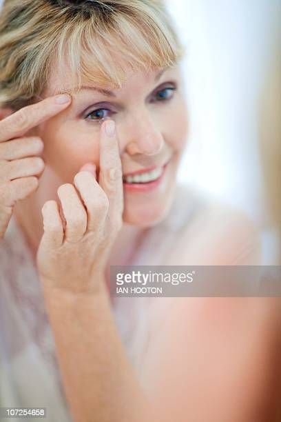 Senior woman putting in contact lenses