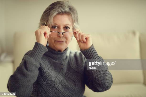 Senior woman putting on her glasses