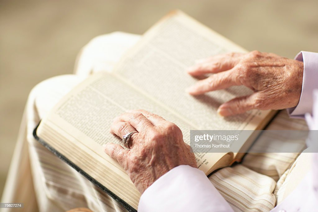 Senior woman reading Bible, mid section, close-up of hands, high angle view