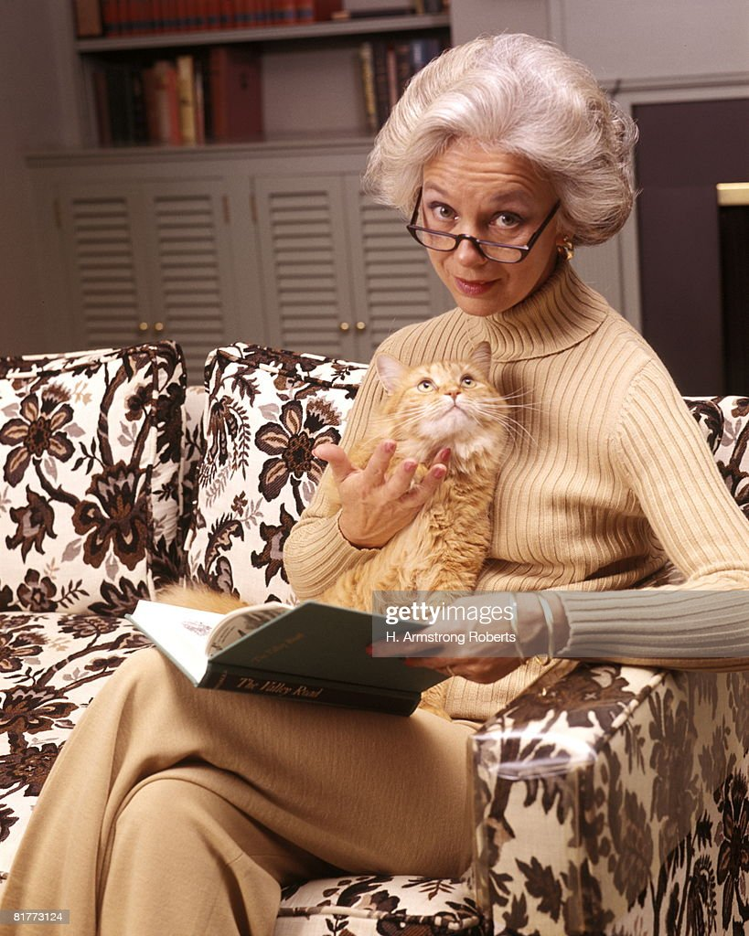 Senior Woman Reading Book Eyeglasses Holding Orange Tabby Cat Lap Couch Living Room Read Pet Pets Cats. : Stock Photo