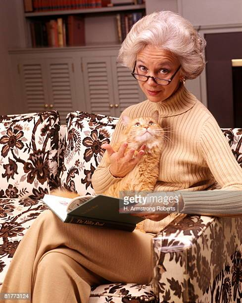 Senior Woman Reading Book Eyeglasses Holding Orange Tabby Cat Lap Couch Living Room Read Pet Pets Cats.