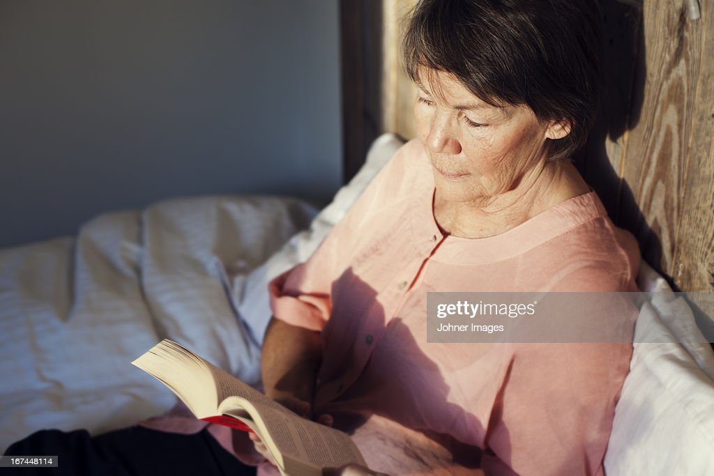 Senior woman reading book in bed : Stock Photo