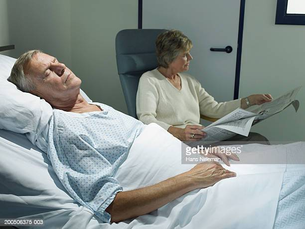 Senior woman reading by senior man asleep in hospital bed