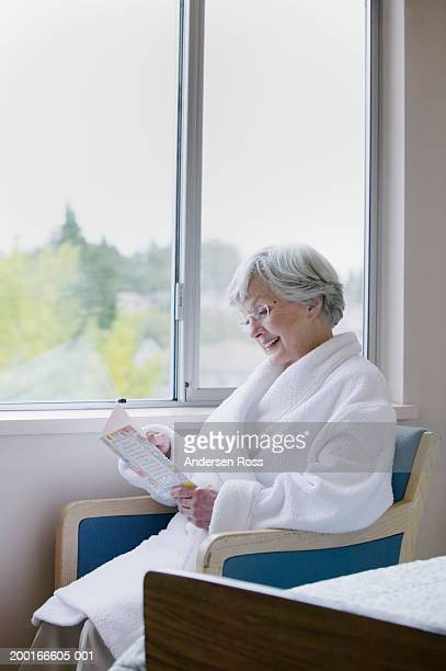 Senior woman reading greeting card beside window in hospital room