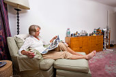 Senior woman reading newspaper while relaxing on armchair at home