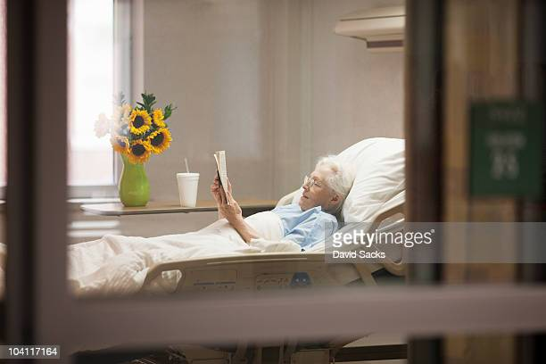 Senior woman reading while lying in hospital bed