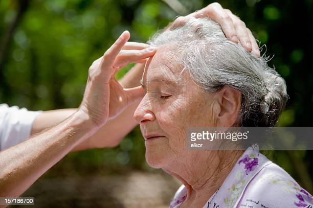 Senior woman receiving head massage outdoors