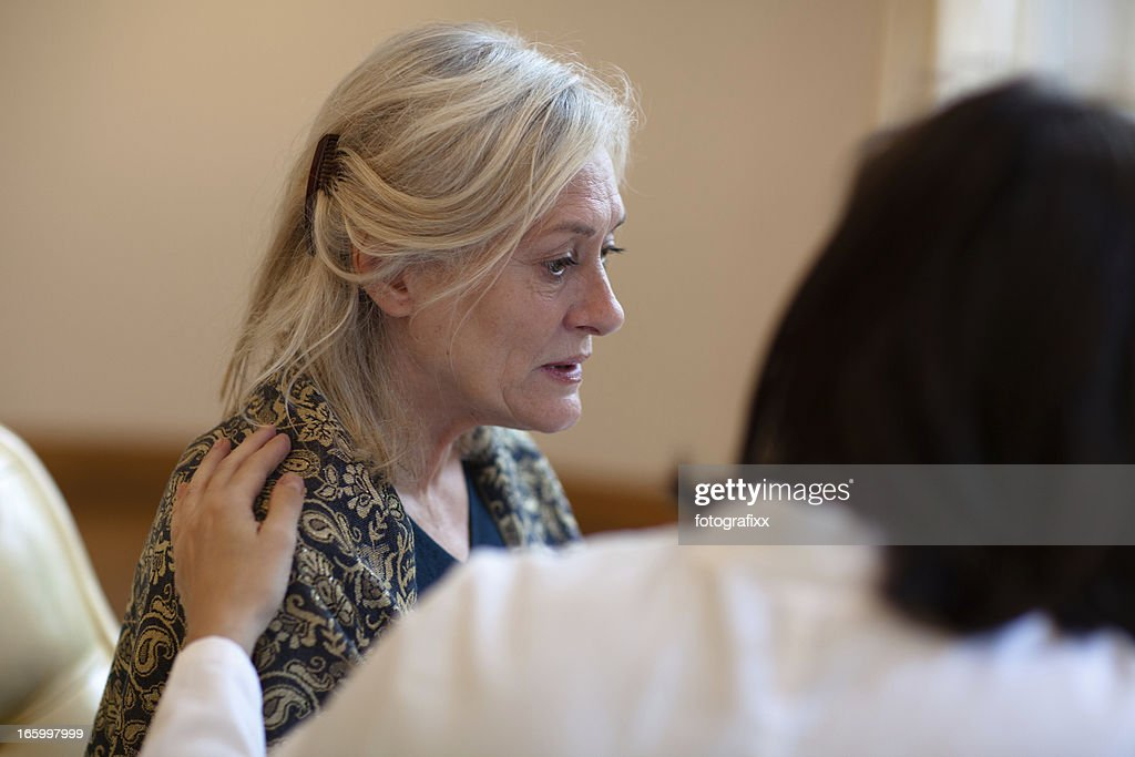 Senior woman receiving help on care home