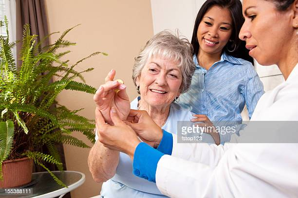Senior woman receiving home physical therapy. Doctor, nurse, therapist.