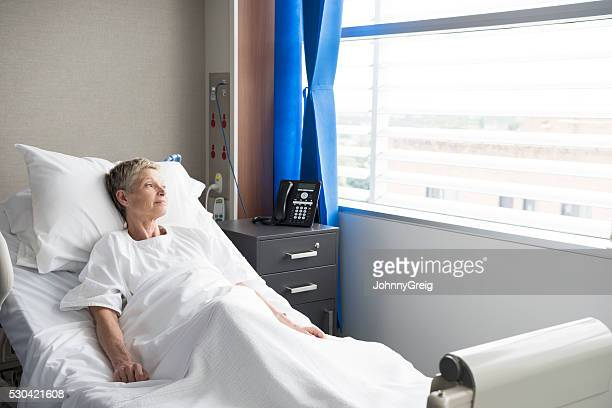 Senior woman recovering in hospital looking through window