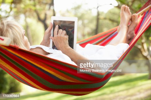 Senior Woman Relaxing In Hammock With  E-Book : Foto stock