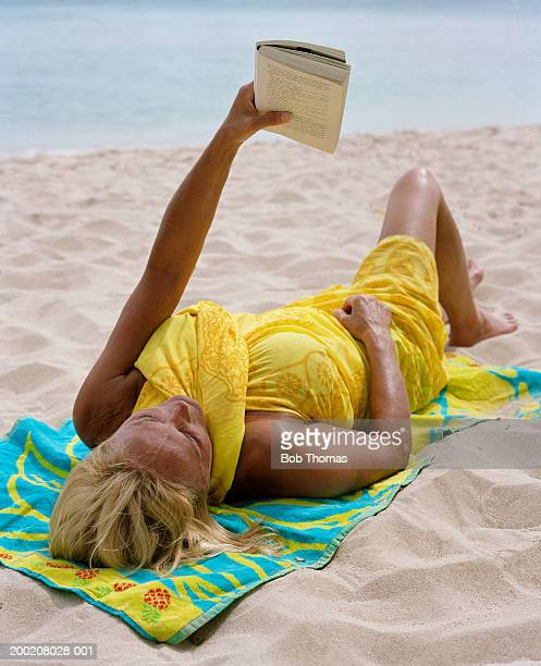 Senior woman relaxing on beach, reading book