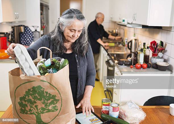 Senior woman removing grocery from shopping bag while using digital tablet in kitchen