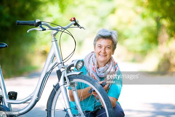 senior woman repairing bike