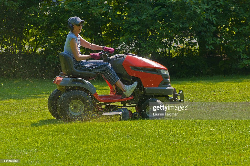 Senior Woman riding a tractor mower on a hot day : Stock Photo