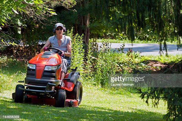 Senior Woman riding a tractor mower on a hot day