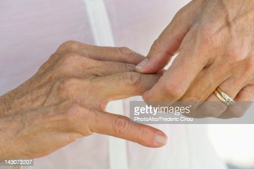 Senior woman rubbing knuckles, cropped