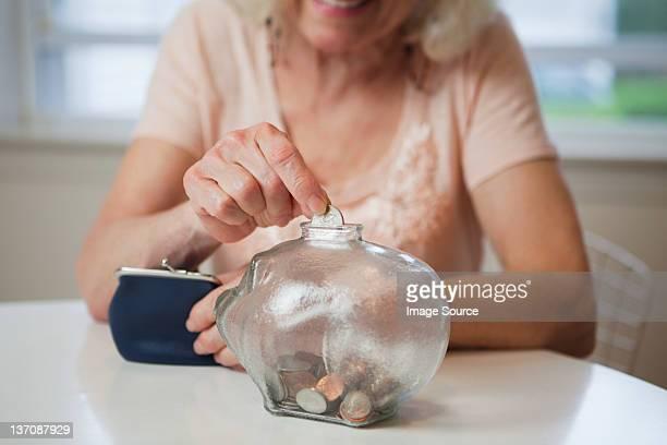Senior woman saving money in piggy bank