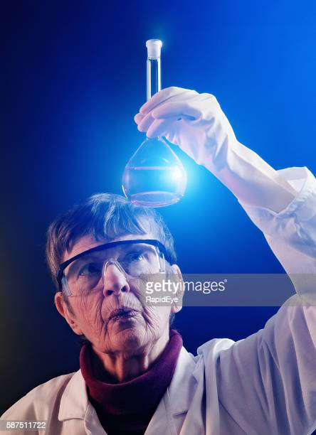 Senior woman scientist studies spotlit fluid in lab flask seriously
