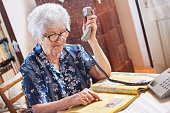Senior woman searching yellow pages and holding telephone.