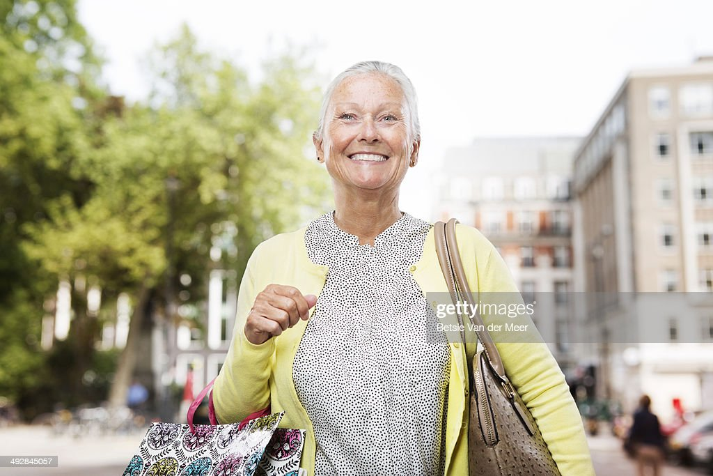 Senior woman shopping in city.