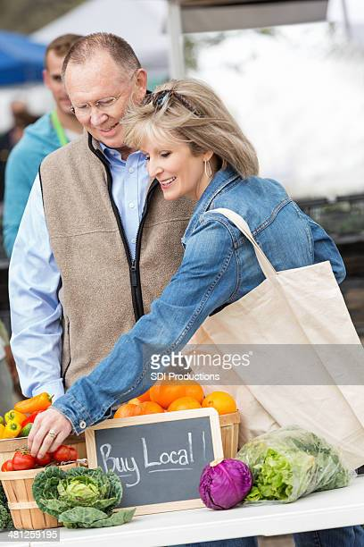 Senior woman shopping with husband at outdoor farmers market