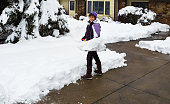 Senior woman shoveling snow from her driveway after snowfall; house in background