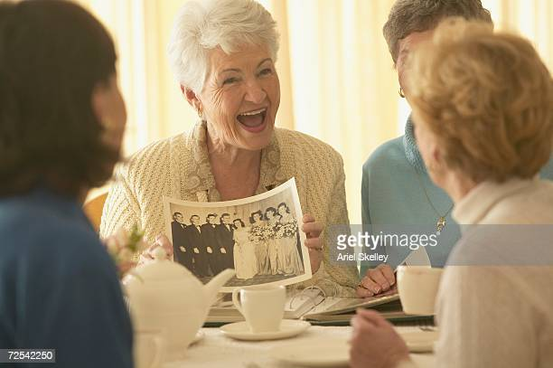 Senior woman showing old photograph to friends