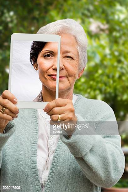 Senior woman showing young lady on digital tablet