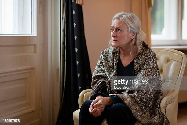 senior Frau sitzt alleine im Wohnzimmer und sieht traurig