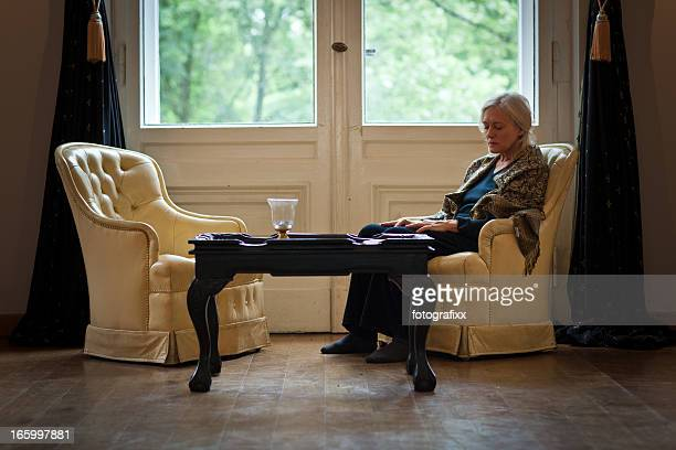 senior woman sits alone in living room and looks sad