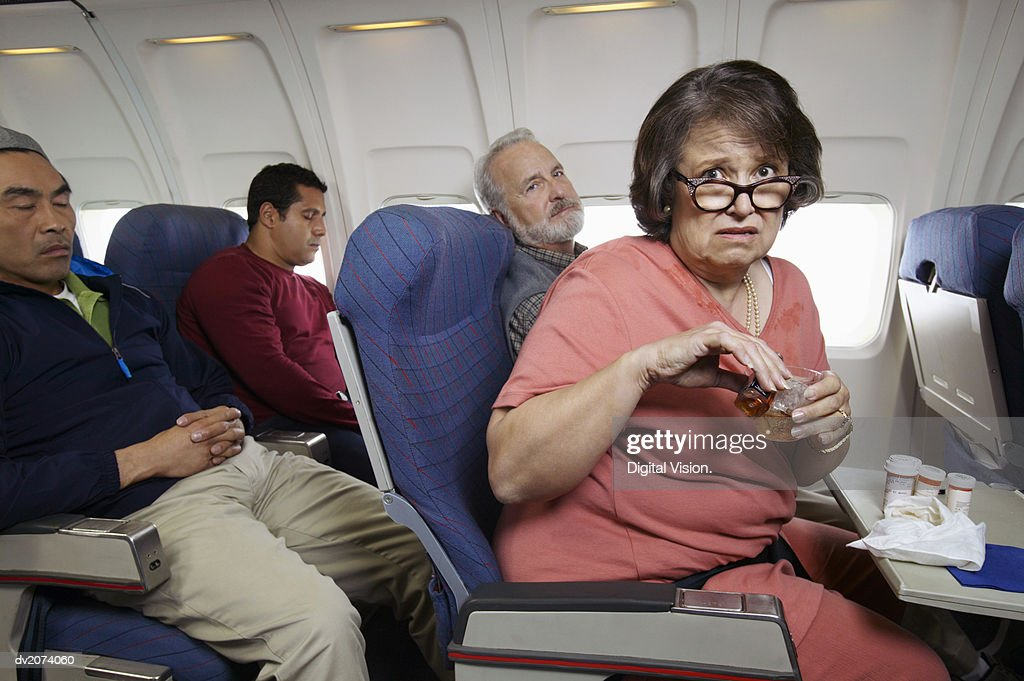 Senior Woman Sits in a Plane, Anxiously Pouring Herself a Whiskey : Stock Photo