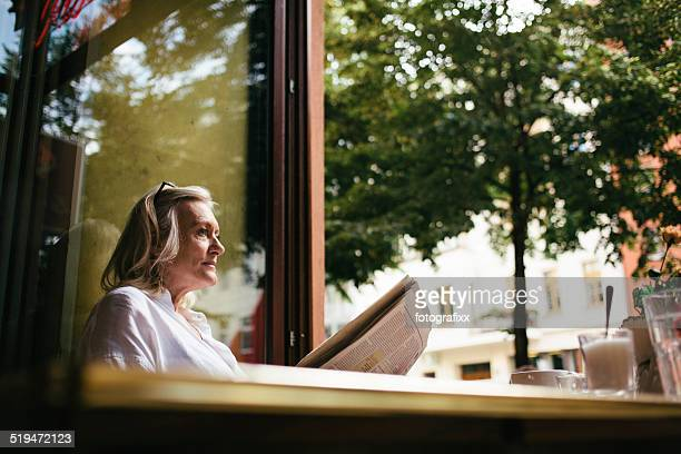 senior woman sits in a Sidewalk Cafe and reads newspaper