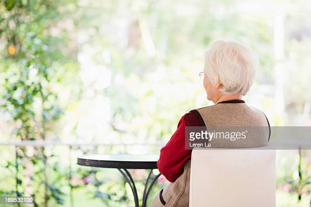 Senior woman sits in the garden